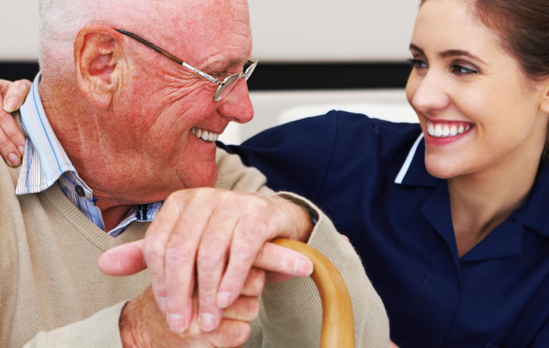 Carer with elderly man smiling